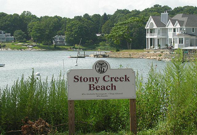 Stony Creek beach sign overlooking the beach at Stony Creek and a beautiful 2 story waterfront home with a dock and stone wall surrounding the home