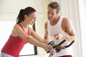Young Couple On Exercise Bike