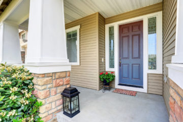 Front entry door with concrete floor porch and flowers pot.
