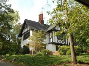 a beautifully landscaped tudor style home located on a tree lined street  in East Rock New Haven CT