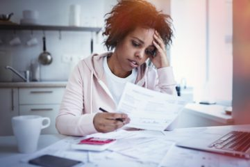 Young african american female sitting at kitchen table with laptop looking at documents wondering why there is so much mortgage paperwork required to get a loan for a home.