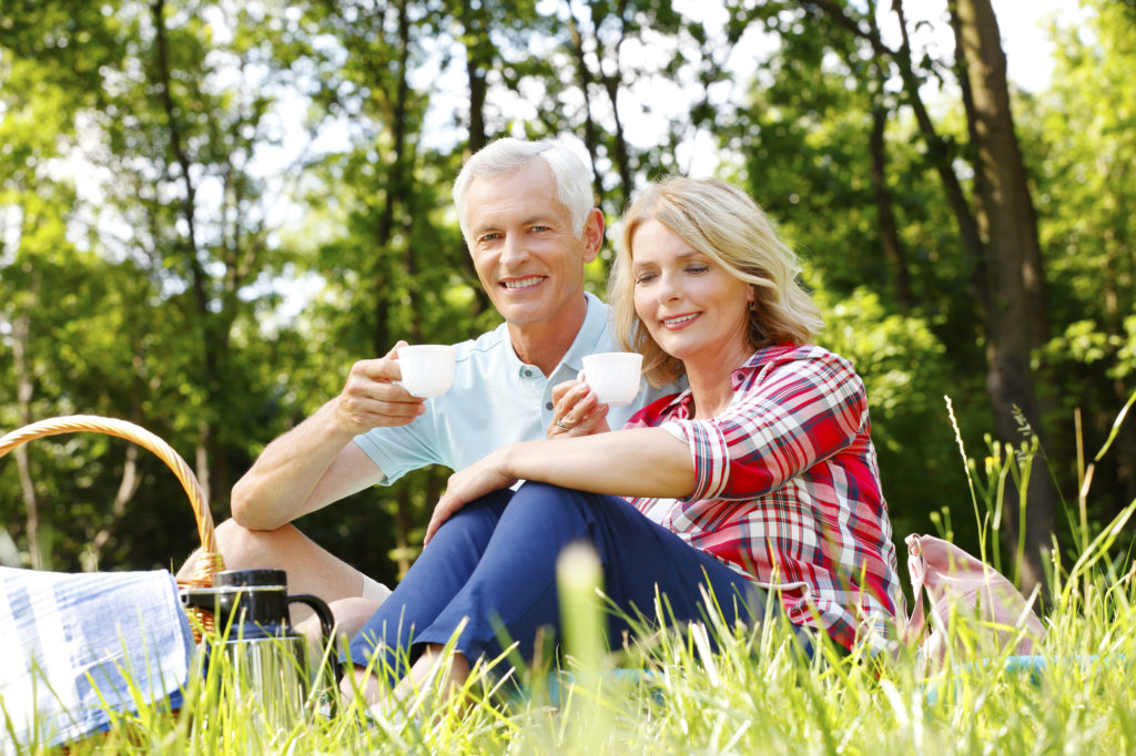 Portrait of active senior hikers relaxing in the woods and drinking coffee. Mature woman and old man sitting on blanket and smiling while looking at camera.