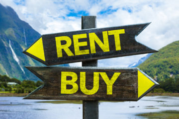 A two-way sign pointing to Buy and Rent, symbolizing being at a crossroads and deciding between buying or renting a house,.